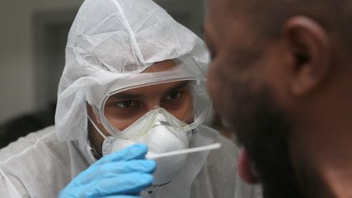 Eine Person in Schutzanzug nimmt einen Rachenabstrich bei einem Mann vor.