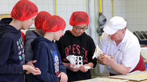 Ausbilder Helfried Marter führt Azubis in das Bäcker-Handwerk ein.