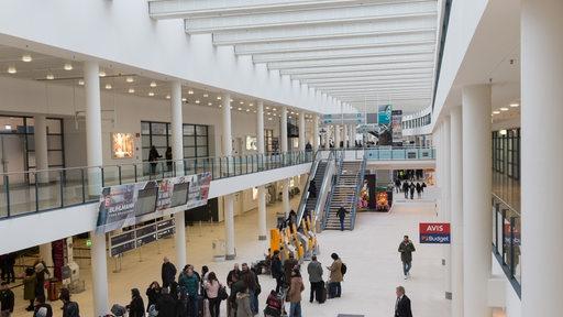 Eine Halle des Bremer Flughafens. Passagiere stehen in einer Warteschlange.