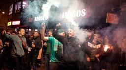 Einige Werder-Fans halten Pyro-Fackel hoch als Hunderte an der Sielwall-Kreuzung den Klassenerhalt feiern.
