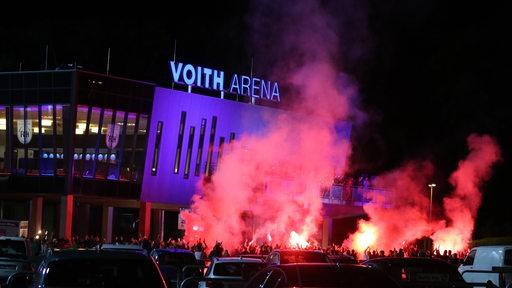 Heidenheim-Fans versammeln sich vor dem Stadion um zünden Pyro-Fackeln, die in der Dunkelheit mit roter Flamme und Qualm aufsteigen.