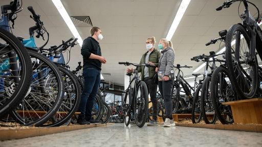 Drei Menschen mit Maske unterhalten sich in einem Laden voller Fahrräder