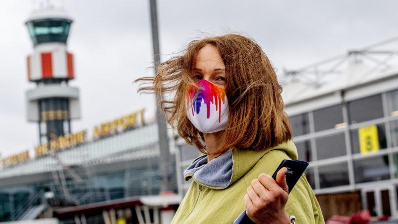 Eine Frau mit Maske vor einem Flughafen