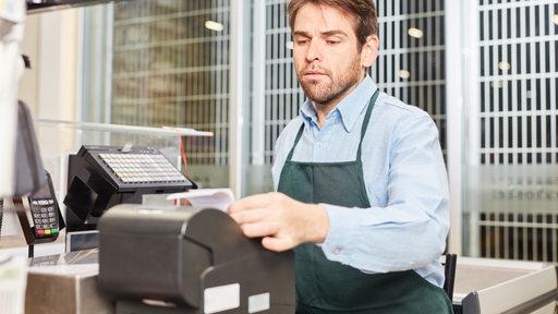 Ein Mann in Schürze an einer Kasse in einem Einzelhandelsgeschäft (Symbolbild)