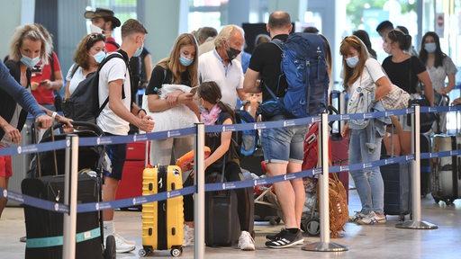 Flugreisende mit Maske stehen in einer Reihe (Archivbild)