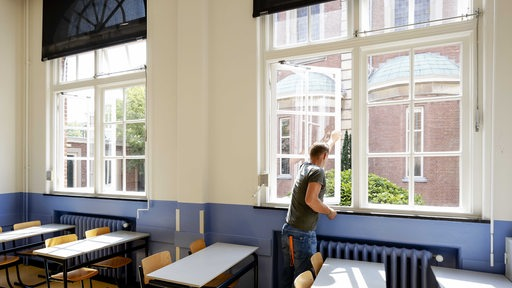 Ein Lehrer öffnet die Fenster eines Klassenraums zum Lüften (Symbolbild)