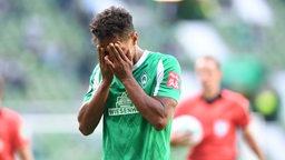 Theodor Gebre Selassie schlägt sich auf dem Spielfeld verzweifelt die Hände vors Gesicht.