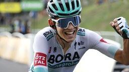 Lennard Kämna reckt auf dem Rad die Faust kämpferisch empor.