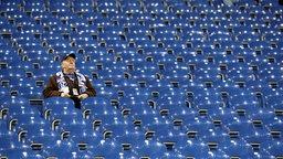 Ein einzelner älterer Schalke-Fan sitzt allein auf der leeren Tribüne in der Arena.