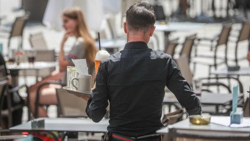 Ein Kellner trägt ein Tablett mit Gläsern. Im Hintergrund sind Tische zu sehen, die meisten von ihnen unbesetzt.