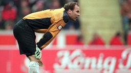 Werder-Torwart Oliver Reck beugt sich nach vorne und stützt sich auf seine Knie ab.