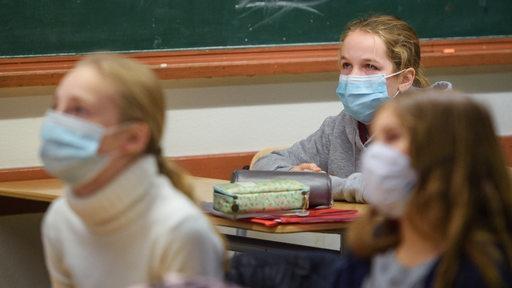Schülerinnen sitzen in einem Klassenzimmer und tragen dabei eine Alltagsmaske