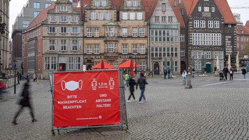 Menschen mit Schutzmasken auf dem Marktplatz. (Symbolfoto)