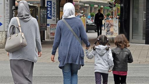 Frauen mit Kopftüchern und zwei Kindern gehen durch die Bremer Innenstadt