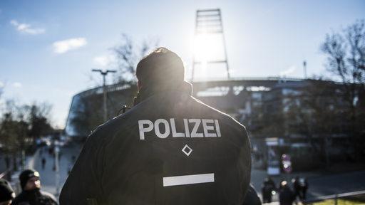 Ein Polizist im Gegenlicht vor dem Weser-Stadion.