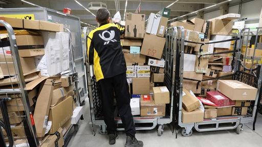 Postmitarbeiter vor Pakethaufen