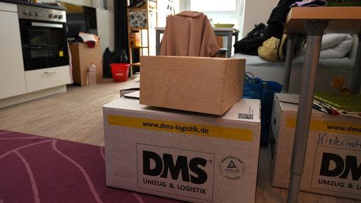 Kisten stehen in einer kleinen Wohnung.
