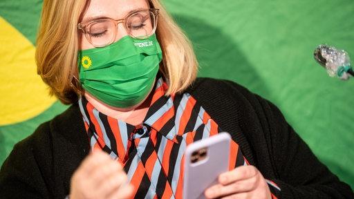 Eine Frau mit einer Maske mit dem Logo der Grünen hält ein Handy in der Hand. | DPA/Sina Schuldt