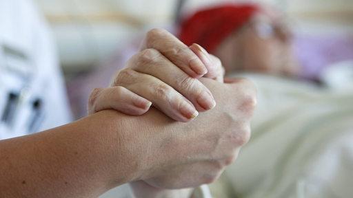 Eine Krankenschwester hält die Hand einer Patientin.