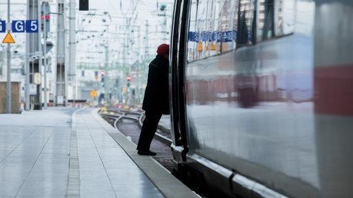 Eine Schaffnerin steigt in einen ICE der Deutschen Bahn.