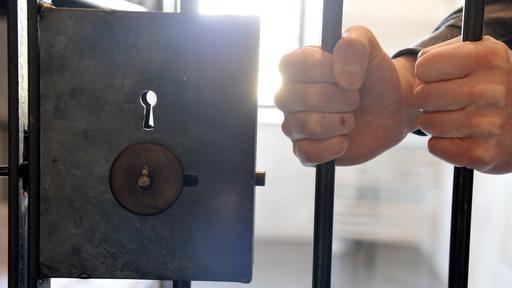 Zwei Hände hinter Gitterstäben einer Gefängniszelle.
