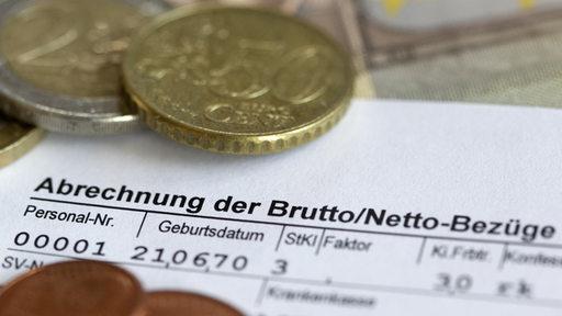 Euromünzen auf einer Lohnabrechnung.