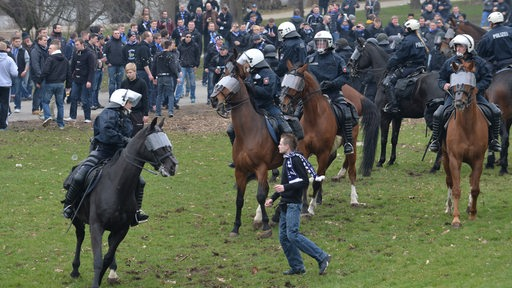 Ein Fan des Hamburger SV versucht am Bremer Weserstadion an berittenen Polizisten vorbei, zu anderen Hamburg-Fans zu gelangen.