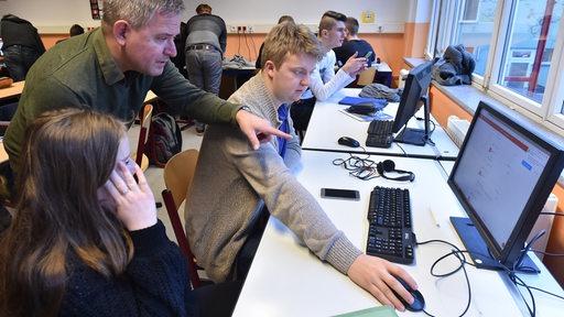 Schüler und Lehrer arbeiten an einem Computer in einem Klassenzimmer