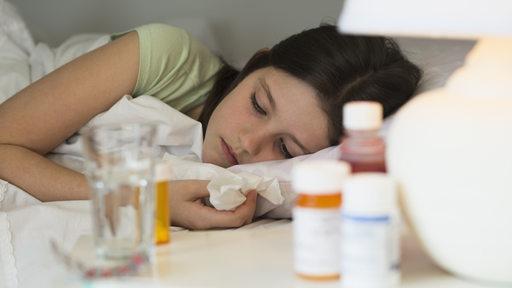 Ein krankes Mädchen liegt im Bett, vor ihr eine Reihe Medikamente auf dem Nachttisch.