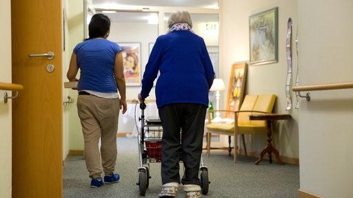 Eine Altenpflegerin und eine Seniorin laufen den Gang eines Pflegeheimes hinunter.