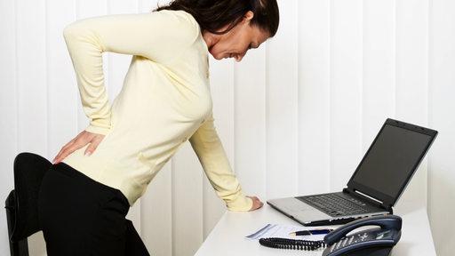 Eine Frau steht vor einem Laptop und hält sich den Rücken
