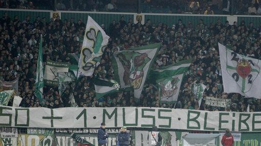 Werder Bremen Fans halten einen Banner mit der Aufschrift ,50+1 muss bleiben, hoch.