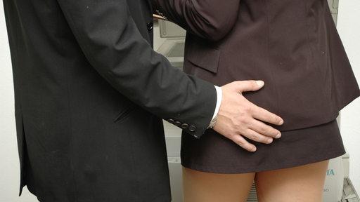 Ein Mann legt einer Frau eine Hand auf das Gesäß.