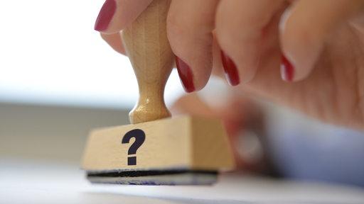 Eine Hand hält einen Stempel mit einem Fragezeichen über einem Dokument.