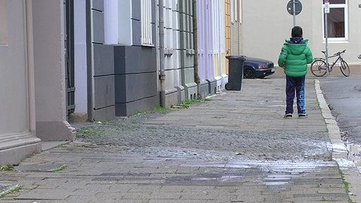 Ein Kind von hinten, auf einem Gehweg