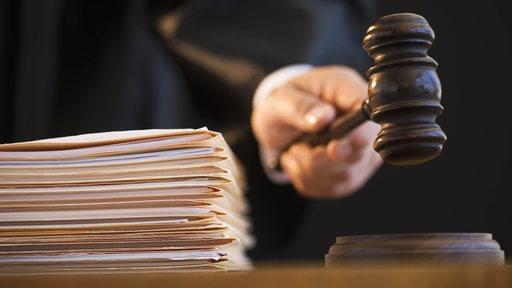 Ein Richter hält einen Richterhammer neben einem Stapel Akten.