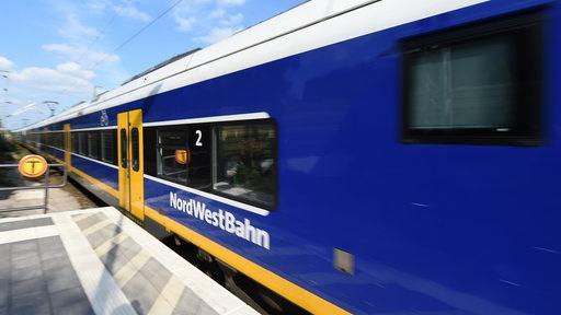 Ein Zug der Nordwestbahn fährt in einen Bahnhof ein.