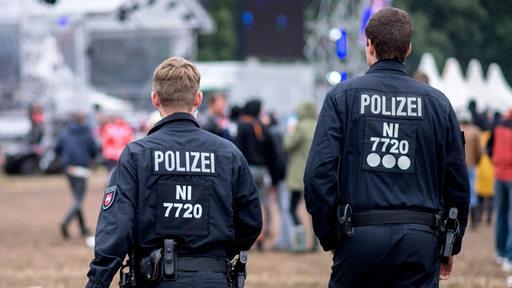Zwei Polizisten stehen auf dem Gelände des Musikfestivals Hurricane in Scheeßel.