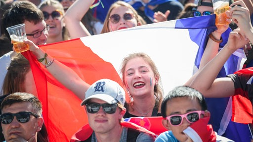 Französische Fans jubeln mit einer Flagge wegen des WM-Titels