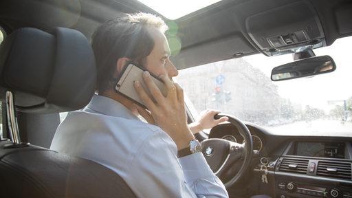 Ein Mann telefoniert in seinem Auto mit seinem Smartphone (gestellte Szene).