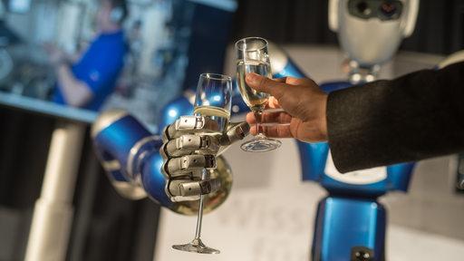 Eine Roboter-Hand und eine menschliche Hand halten Sektgläser in den Händen und stoßen an