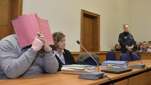 Niels H. sitzt vor Gericht auf der Anklagebank und hält sich eine Mappe vor das Gesicht und ist von Pressevertretern umringt.
