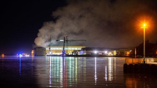 Rauch steigt in den Nachthimmel über der Lürssen-Werf in Bremen auf.