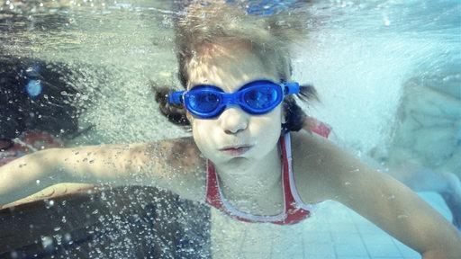 Ein Kind mit Schwimmbrille taucht