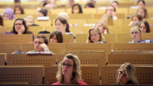 Junge Männer und Frauen sitzen auf Plätzen in einem Hörsaal. (Symbolbild)