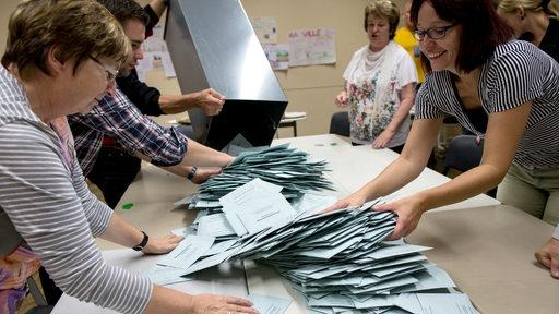 Eine Gruppe Wahhlhelfer leeren eine Wahlurne auf einem Tisch aus, um die Stimmen zu zählen.