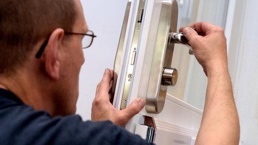 Ein Mitarbeiter eines Schlüsseldienstes schraubt an einem Türschloss.