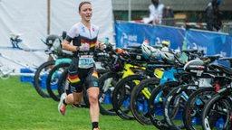 Duathlon-Weltmeisterin Merle Brunnee läuft im Regen und kommt bei der Radstation an.