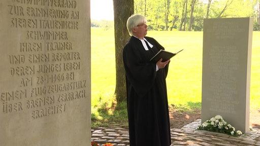 Der neue Gedenkstein wird durch den Priester eingeweiht.