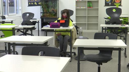 Die 6.-Klässlerin Alina Stoll sitzt ganz alleine im Klassenzimmer mit Maske und Ipad.